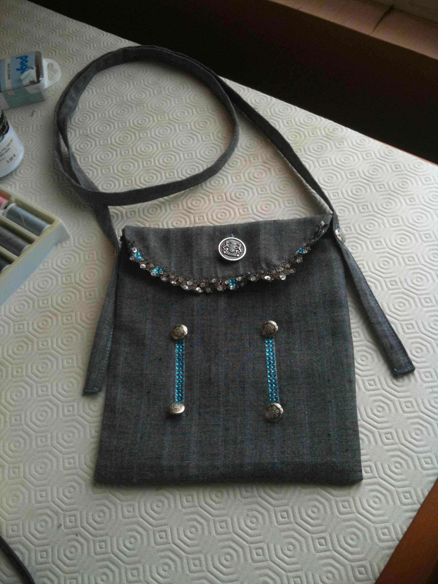 Pochette tons gris, agémentée de petits boutons argentés et straas bleus