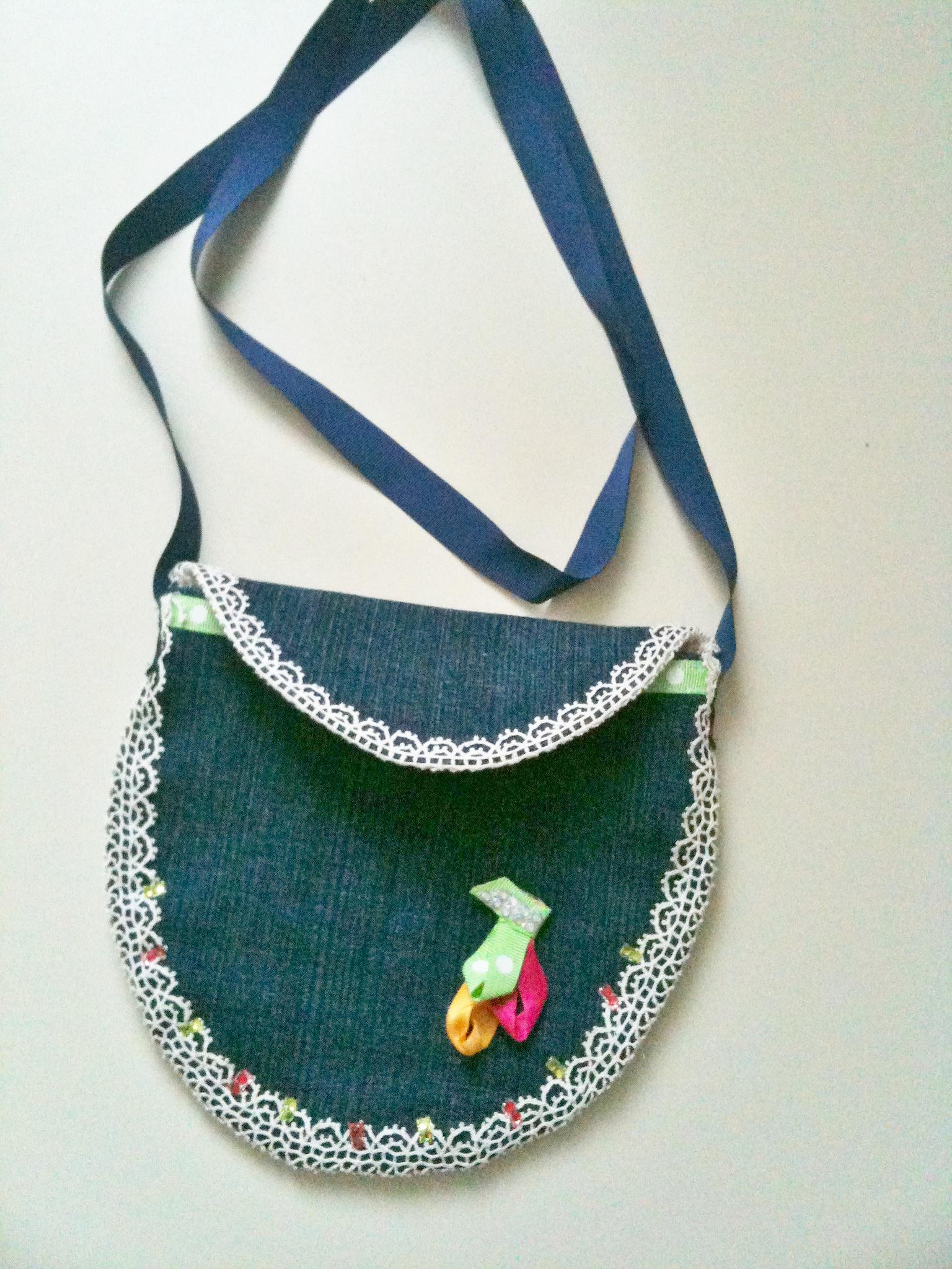 Petite pochette, jean foncé bleu, ovale, doublée fond blanc et petites fleurs colorées, décor dentelle strass et ruban.
